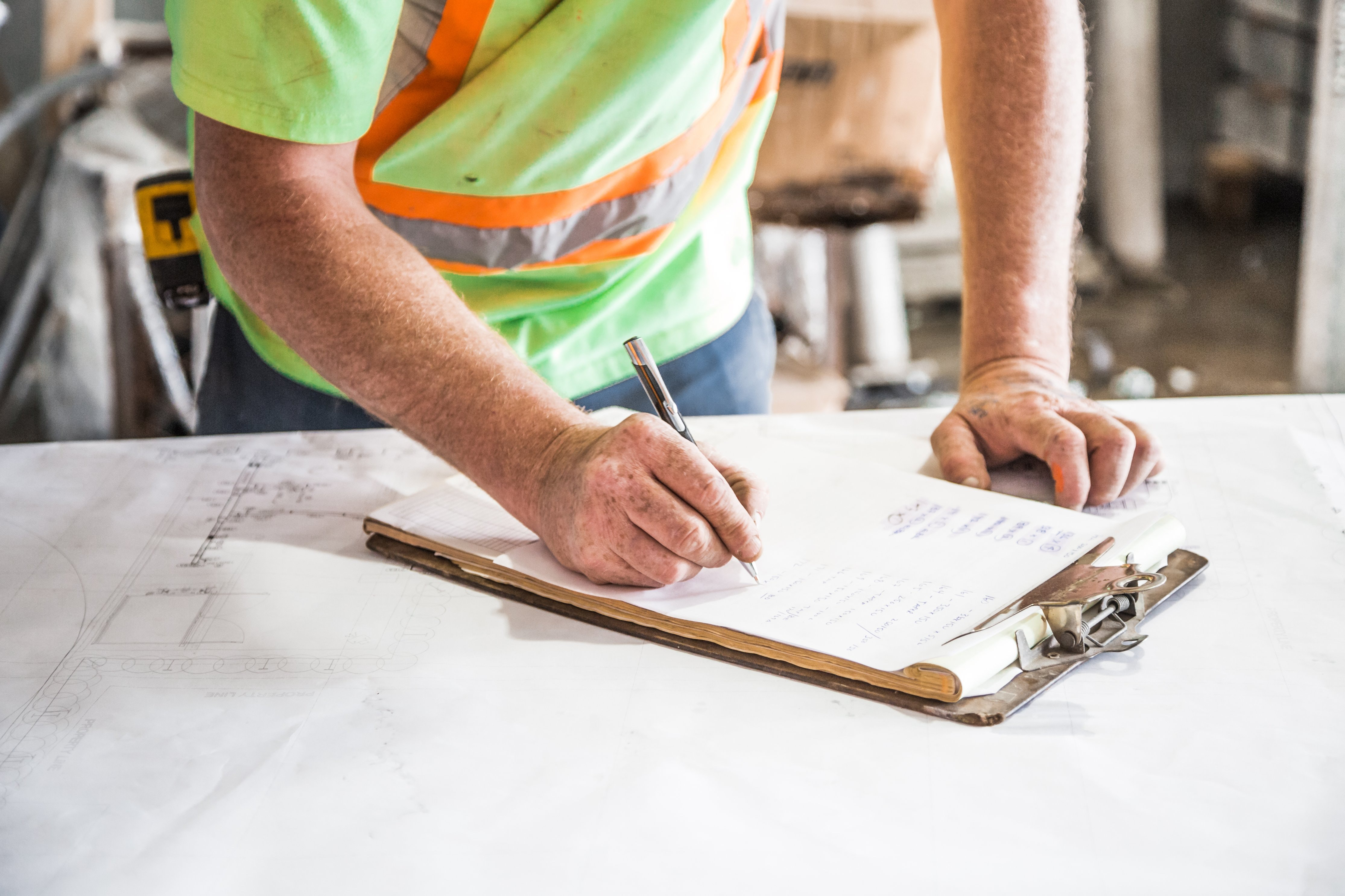 construction worker in green vest writing on clipboard